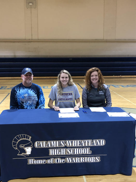 Grace E. sigining with parents to continue atheltic and academic career